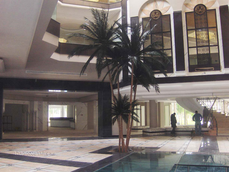 image of a artificial  palm tree by a pool